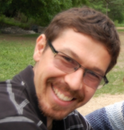 A photo of Dimitri Kaasan-Stull, who is wearing glasses and wearing a striped polo shirt